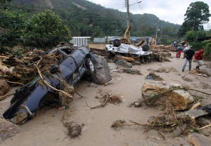 Residents walk past destroyed cars after a landslide in Teresopolis January 13, 2011. The death toll from the devastated mountainous region near the city of Rio de Janeiro was expected to rise as rescuers reached the more remote areas. Heavy rains earlier in the week killed 13 people in Sao Paulo state, bringing the total number of deaths in southern Brazil to at least 369. REUTERS/Bruno Domingos (BRAZIL - Tags: DISASTER IMAGES OF THE DAY)